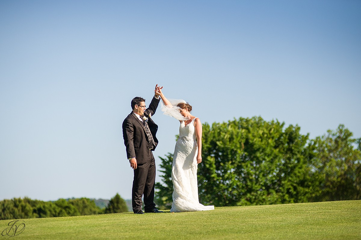 bride and groom dancing outside on golf course