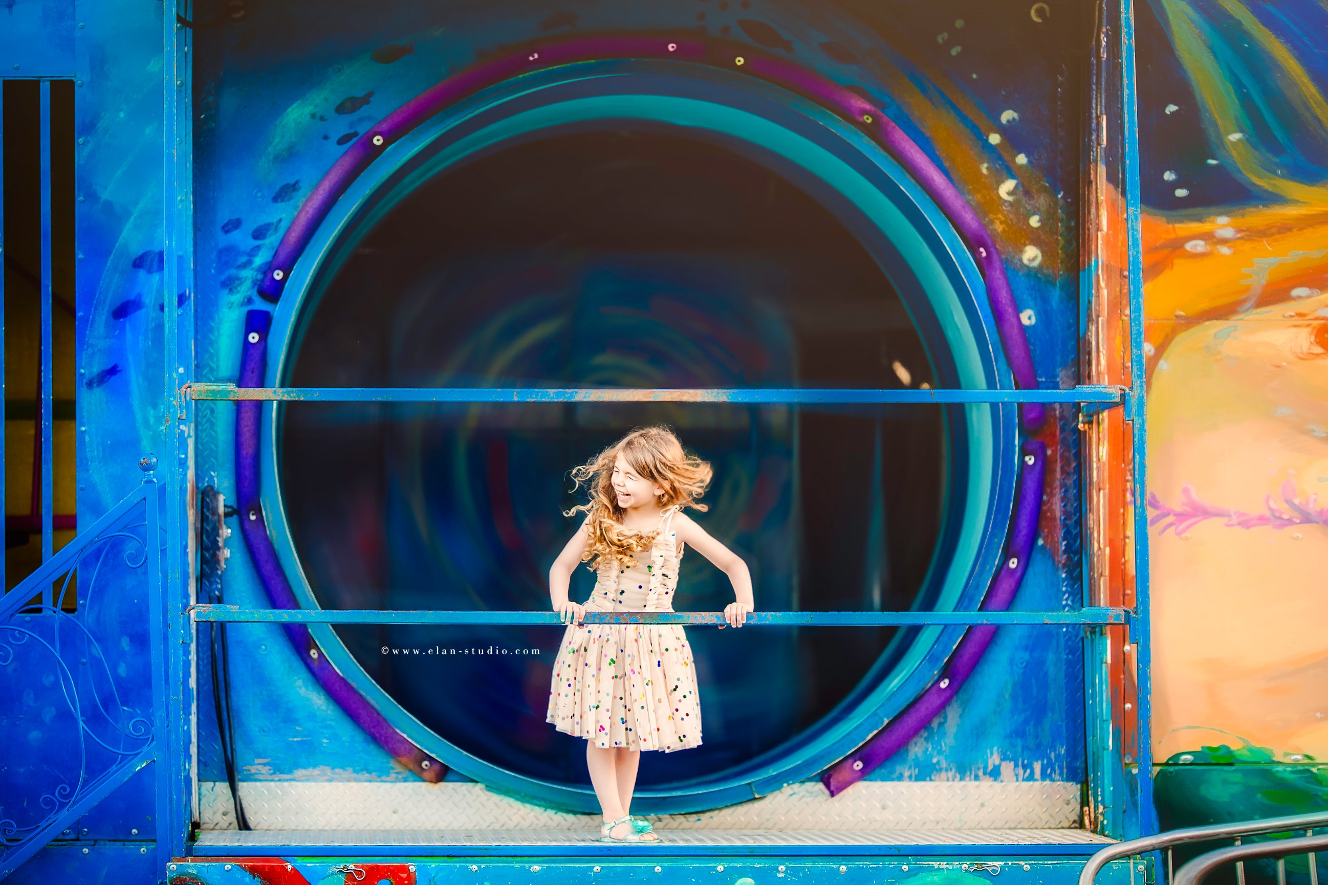 happy girl in front of painted carnival fun house