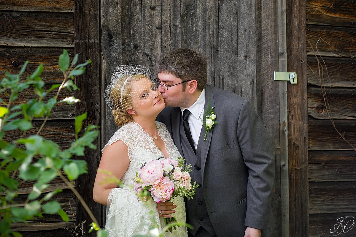 beautiful image of groom kissing bride on the cheek