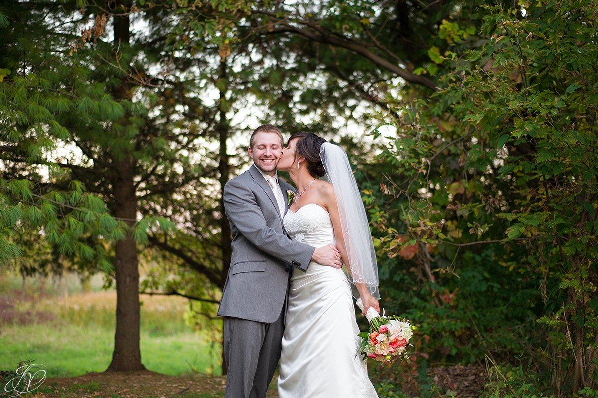 cute photo of bride kissing groom on the cheek