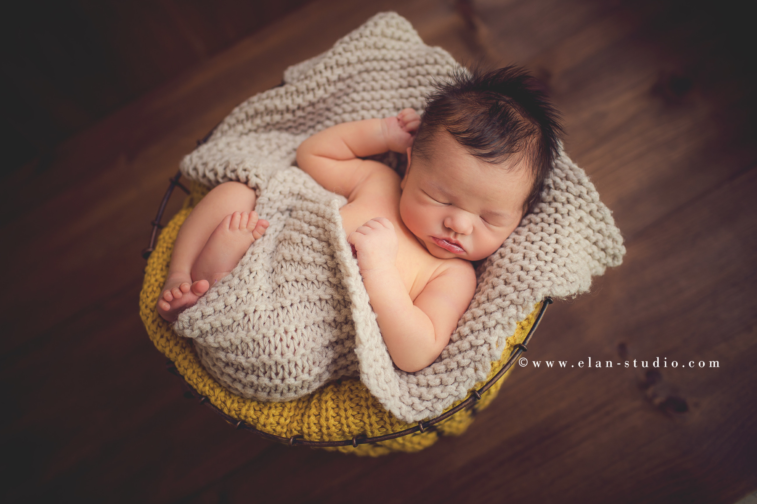 newborn baby with lots of hair, wrapped in oatmeal and mustard, in basket