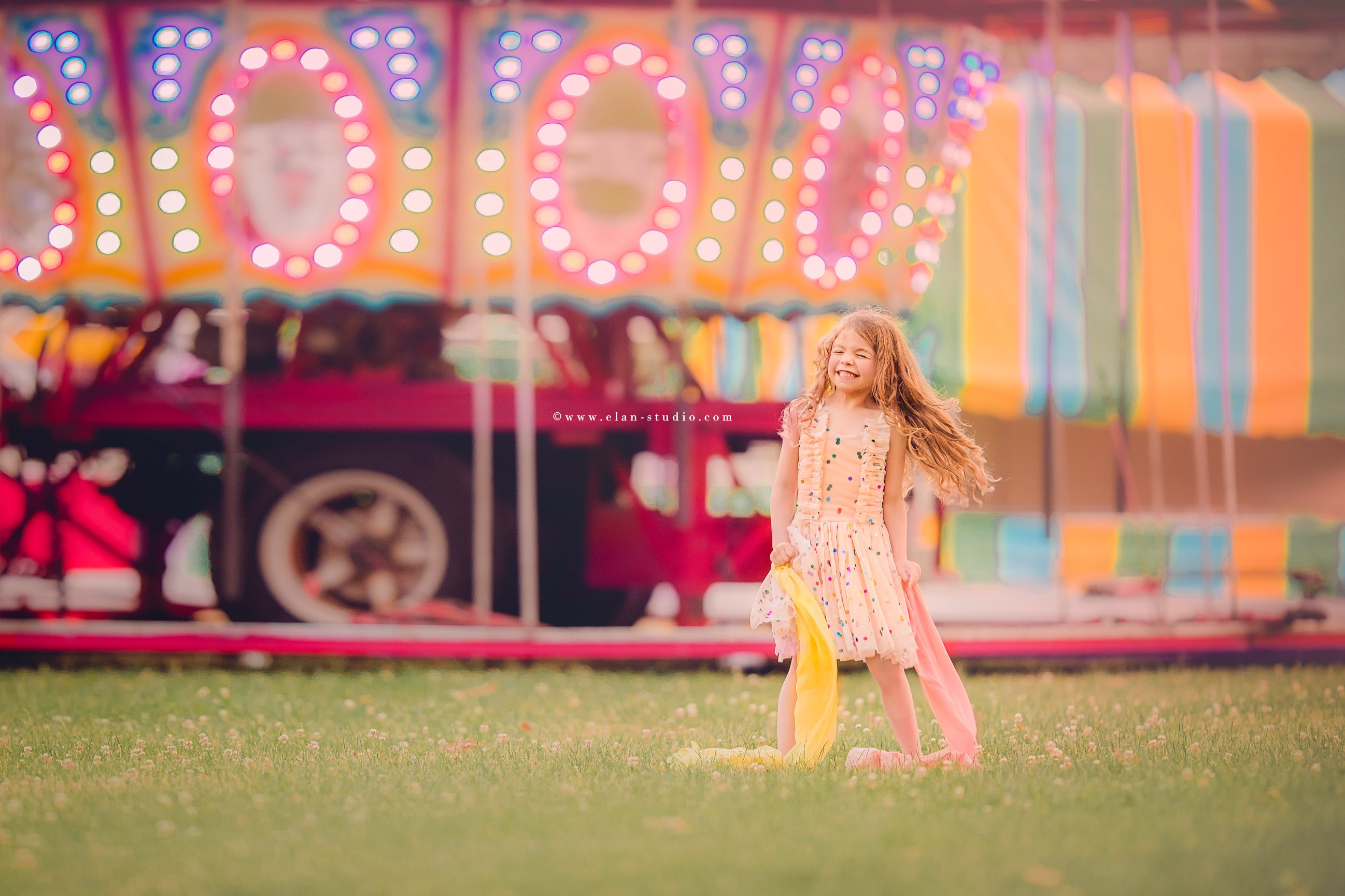 little girl with long hair, on grass at circus, with carousel behind her