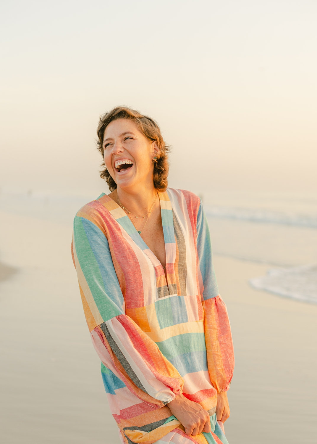 cancer survivor laughing and wearing a long rainbow dress, Ryaphotos