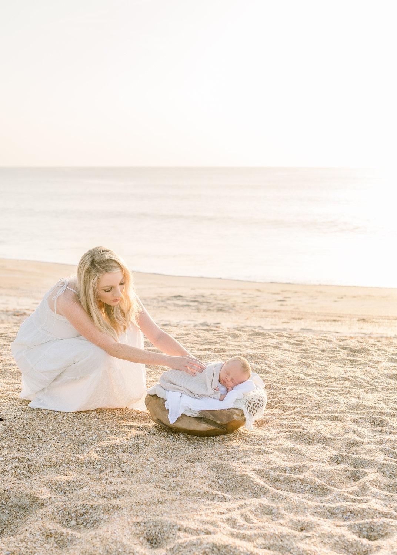 mother tucking newborn boy into cradle, wooden cradle prop, Ryaphotos