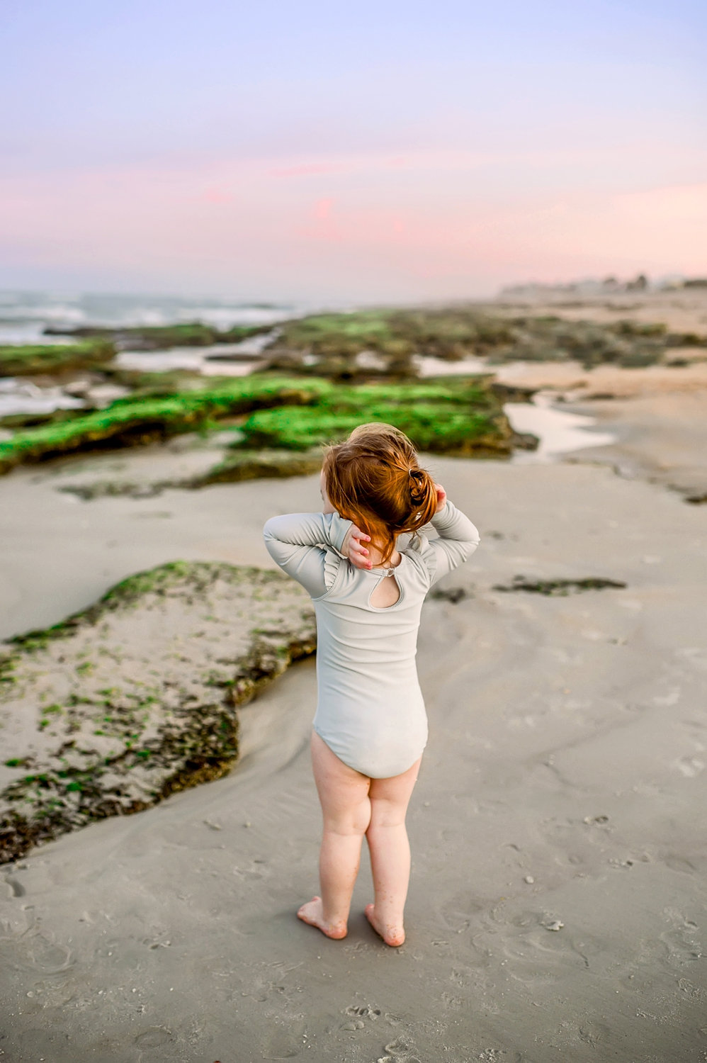 little girl staring out at rocky, mossy coastline, Florida, Ryaphotos