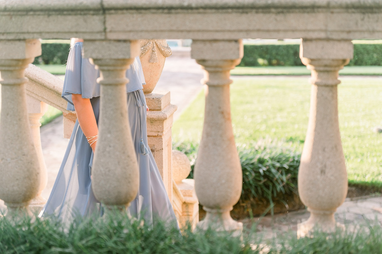 peek at a walking pregnant woman through stone architectural columns in a manicured garden